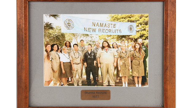 "Framed group photo of the 1977 DHARMA recruitsThe photograph shows the 16 new DHARMA recruits from 1977, featuring prominently Jack, Kate and Hurley, who somehow landed on the Island in that year while on board the Ajira Airways Flight 316 to Guam, with Frank Lapidus as the pilot, in the episode, ""Namaste.""Related content:EPISODE RECAP - ""Namaste""PHOTOS - ""Namaste""EPISODE RECAP - ""Follow the Leader"""