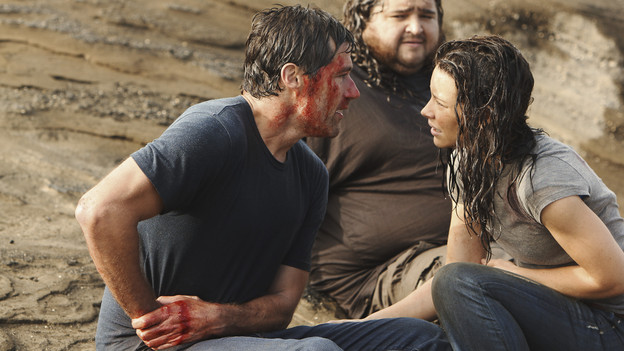 Jack and Kate sitting on the ground, with Hurley sitting behind them, watching. Jack is bloody and is holding his side, Kate looks concerned.