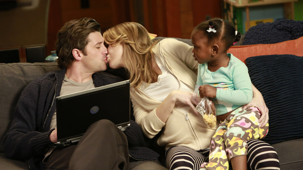 Derek, Meredith, and Zola share some family time on the couch.