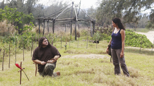 Screencap from LOST: Hurley is crouched on the ground next to a grave on the island, looking up and talking to Ilana.