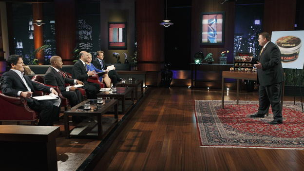 "SHARK TANK -""Episode 204"" -- Tempers flare when guest Shark Mark Cuban urges the entrepreneurs to stop negotiating with the other Sharks if they even want a chance to make a business deal with him. In this episode, a fireman from Arkansas brings an invention to the Shark Tank that could make millions and save lives; after creating an eco-friendly way to listen to music on the go, a duo from Chicago hope the Sharks will want to invest; a feisty, combative entrepreneur from Montclair, New Jersey seeks to cash in on the lucrative wedding business; and a man from Oklahoma hopes the Sharks will smell the money when he pitches his unique male-oriented brand of candles, on ""Shark Tank,"" FRIDAY, MAY 6 (8:00-9:00 p.m., ET) on the ABC Television Network. (ABC/CRAIG SJODIN)MARK CUBAN, DAYMOND JOHN, KEVIN O'LEARY, BARBARA CORCORAN, ROBERT HERJAVEC, JOHNSON BAILEY (MAN CANDLE)"
