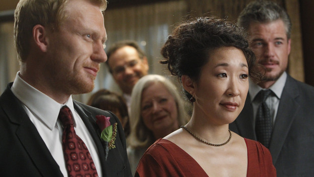 "Cristina and Owen get married!  Cristina opted not to wear a white dress because she thought it was ""sexist and vaguely racist."" The happy couple walked down an aisle created by a line of all their friends. Rings were exchanged and tears of happiness flowed."