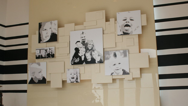 "Family Photo Collage WallOne of the main elements in the Music Studio of the Wagstaff's new home is a photo collage. Ty used family photos to create a 3D art piece that became a great focal point for the room.  Materials: (4) sheets of 1/2"" MDF or plywood8-12 Enlarged Black and White photosTools:Table sawGlue, nails, or screwsHammer or drillSpray AdhesivePrimerPaint (in desired color)To Begin:1) Start by collecting photos of your family, pets, flowers, or anything you would like to display on your walls. 2) Once you have your images selected, they need to be cropped, enlarged and turned in to black and White images.   You will need approximately 1-2 of each size. (12""x12"", 14""x14"", 16""x16"", 20""x20"", and one large 24""x24"" or 30""x30"")  3) Cut out squares and rectangles of plywood or MDF.  You will need enough to mount your photos to as well as extra to layer on top of each other.  (4 8""x8"", 4 10""x10"", 4 12""x12"", 4 14""x14"", and similar sizes in rectangles)4) Prime and paint all your pieces and one full sheet of plywood, we used Navaho White but any light color will work good to create contrast between the board and the picture. 5) Mount your photos to the squares with acid-free spray adhesive. 6) Lay out the painted sheet of plywood and arrange your squares evenly like in the picture provided. Layer squares on top of each other to create depth and be sure to overlap squares. 7) Have your mounted photos ready and place them as you go, mounting them with glue or nails.  Allow adequate time to dry before you mount this to the wall. 8) Touch up any nail holes or fill and paint any screw holes. 9) The best way to attach this to a wall is with a French cleat."